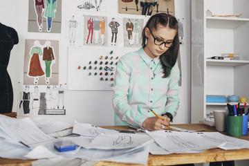 Beautiful fashion designer drawing sketch at workbench in studio