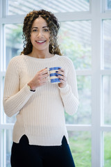 Woman standing near window holding coffee cup