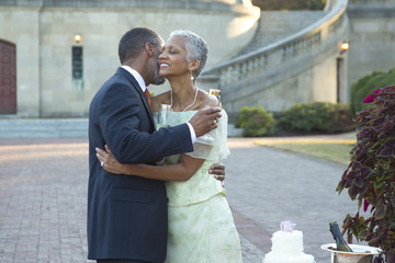 Black couple hugging near wedding cake