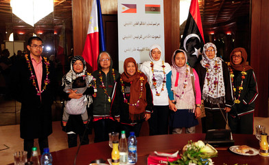 Filipino nurses, who were freed from Islamic State militants by Libyan forces in Sirte, pose for a group photo during a handover ceremony in the presence of a Filipino envoy in Tripoli