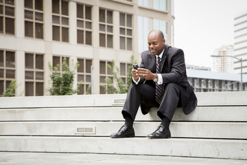 Black businessman sitting on staircase texting on cell phone outdoors