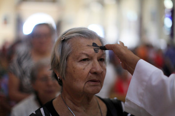 A Catholic faithful has her forehead marked with ash during a mass for Ash Wednesday at the San Salvador Cathedral in San Salvador