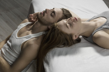 High angle view of couple with closed eyes relaxing on bed