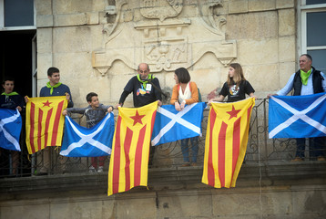 People hang Scottish and Catalan flags from a balcony during the Basque nationalist celebration Aberri Eguna (Fatherland Day), organised by the Red Independistak (Independence Network) in Guernica