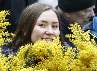Woman carries bunches of mimosa ahead of International Women's Day near Rizhsky flower market in Moscow
