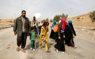 Displaced Iraqis flee their homes in Mamoun district as Iraqi forces battle with Islamic State militants, in western Mosul,