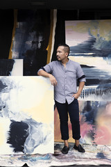 Pacific Islander artist leaning on paintings