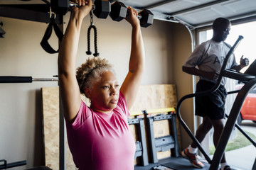 Black couple lifting working out in garage