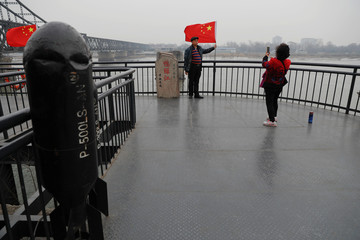 Tourists stand beside a Chinese flag taking pictures on the Broken Bridge in Dandong
