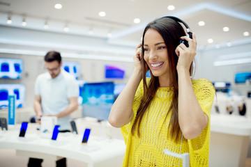 Spoed Foto op Canvas Muziekwinkel Beautiful female at tech store looking for a new peace of gadget. Buying new headphones.