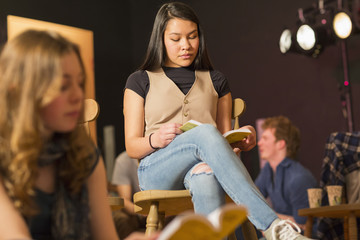 Mixed Race teenage girl reading script in theater class