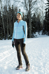 Black runner listening to cell phone with earbuds in winter