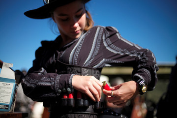 Jessica Healey, 12, under the character name 'Rosebud', loads shotgun shells on her belt during competition at the Women of the West shooting contest at the Namoi Pistol Club in Gunnedah in rural New South Wales