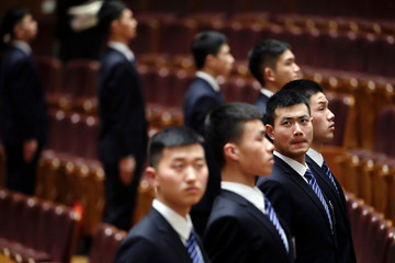 Security personnel wait for reporters and guests to leave the Great Hall of the People after the opening session of the Chinese People's Political Consultative Conference (CPPCC) in Beijing