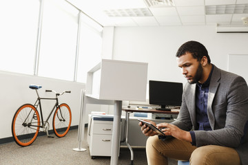 Mixed Race man using digital tablet in office