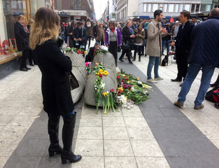 People put flowers near the crime scene in central Stockholm