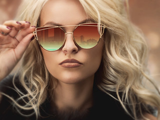 Portrait of a beautiful young blond woman in sunglasses. Photo closeup
