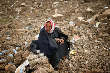 A displaced Iraqi waits to get into Hamam al-Alil camp, on a rainy day, south of Mosul