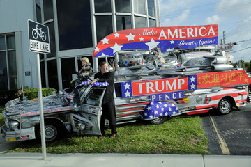 A supporter of U.S. President Donald Trump stands on sidewalk as Trump's motorcade passes by in West Palm Beach