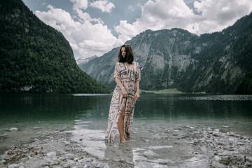 Caucasian woman wading in near mountain lake