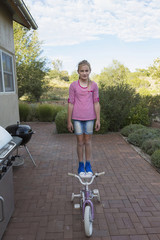 Caucasian girl standing on seat of bicycle