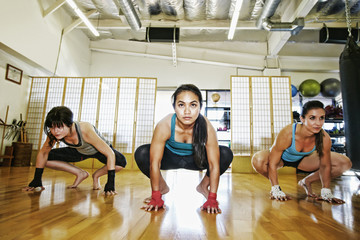 Women crouching on floor of gymnasium