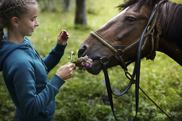 Caucasian girl holding flowers for horse to smell