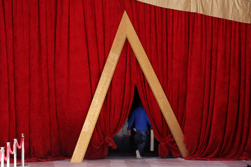 A worker walks through a curtain on the red carpet outside the Dolby Theatre as preparations continue for the 89th Academy Awards in Hollywood