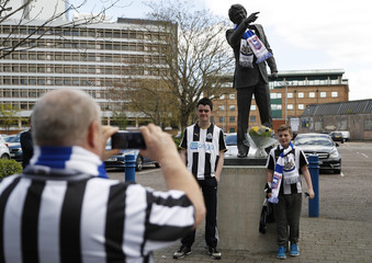 Newcastle United fans take a photograph in front of the statue of Sir Bobby Robson outside the stadium before the match
