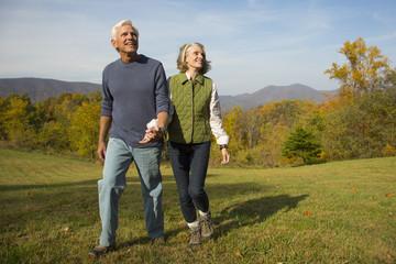 Older Caucasian couple walking in field
