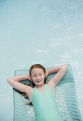 Caucasian girl floating on pool raft in swimming pool
