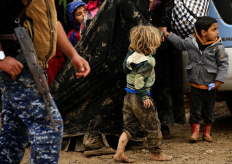 A displaced Iraqi child who fled his home with his family during a battle between Iraqi forces and Islamic State militants, walks with his mother at a checkpoint to be transfer to Hammam al-Alil camp, in Mosul