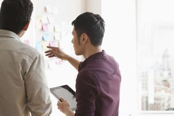 Businessmen with digital tablet talking at whiteboard