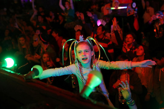 A girl watches as floats pass during the Bacchus parade during Mardi Gras in New Orleans, Louisiana