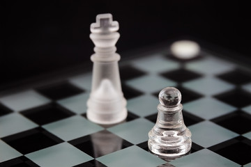 the chess pieces of glass: the opposition pawns and king on a black background.