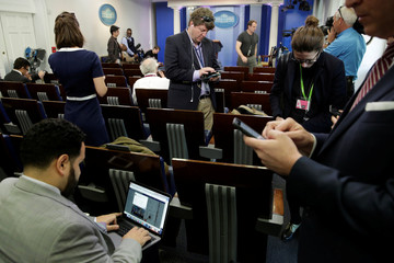 Journalists work in the briefing room