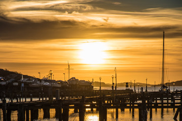 Orange and yellow sky above harbor port sunset boats