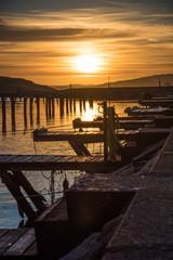 Orange and yellow sky above harbor port sunset dock
