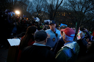 A U.S. Park Police officer pushes back demonstrators as they rally against the Trump administration's new travel ban outside of the White House in Washington