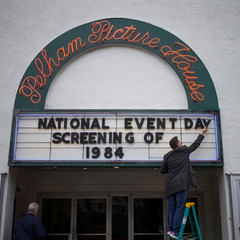 Man places letters on a sign board ahead of screening for the movie 1984 in Pelham, New York