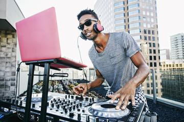 Smiling Black DJ on urban rooftop