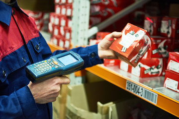 warehouse worker scanning automobile spare part with laser barcode scanner