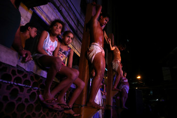 Residents attend a re-enactment of the Via Crucis during Good Friday celebrations in the Rocinha slum in Rio de Janeiro
