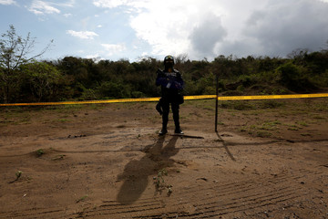 A police officer stands guard on a plot of land where skulls were found at unmarked graves on the outskirts of Veracruz