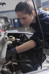 Hispanic mechanic repairing car engine