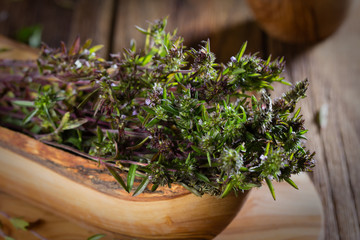 Fresh thyme in olive wooden bowl. Toning