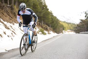 Cyclist man riding mountain bike on a mountain road.