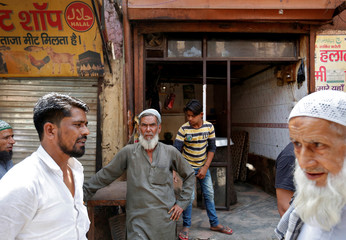 A muslim meat shop owner looks on outside his closed shop in Gurugram