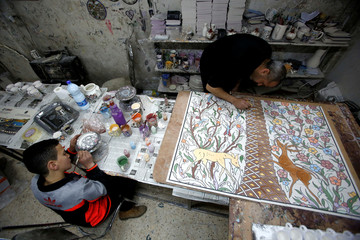 Palestinians paint ceramics in Al-Okhowa pottery shop in the West Bank city of Hebron