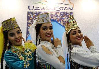 Models pose at the Uzbekistan booth at the International Tourism Trade Fair ITB in Berlin